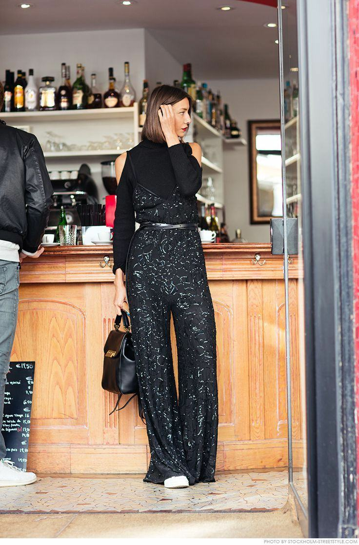 The girl is wearing a black turtleneck with cutouts on the shoulders, a black jumpsuit with puffy trousers decorated with beads and a thin leather belt, white sneakers, and a black leather bag.