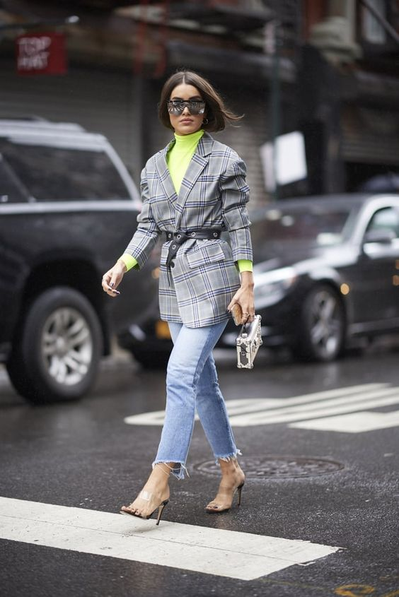 The girl is wearing a bright neon turtleneck with a collar, a gray checkered long jacket with accordion sleeves,