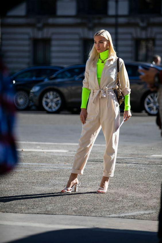 The girl is wearing a bright neon turtleneck with a collar, a beige cotton suit with three-quarter sleeves with a belt and a deep neckline, white sandals with thick high heels and thin straps, a gold chain and a belt bag.