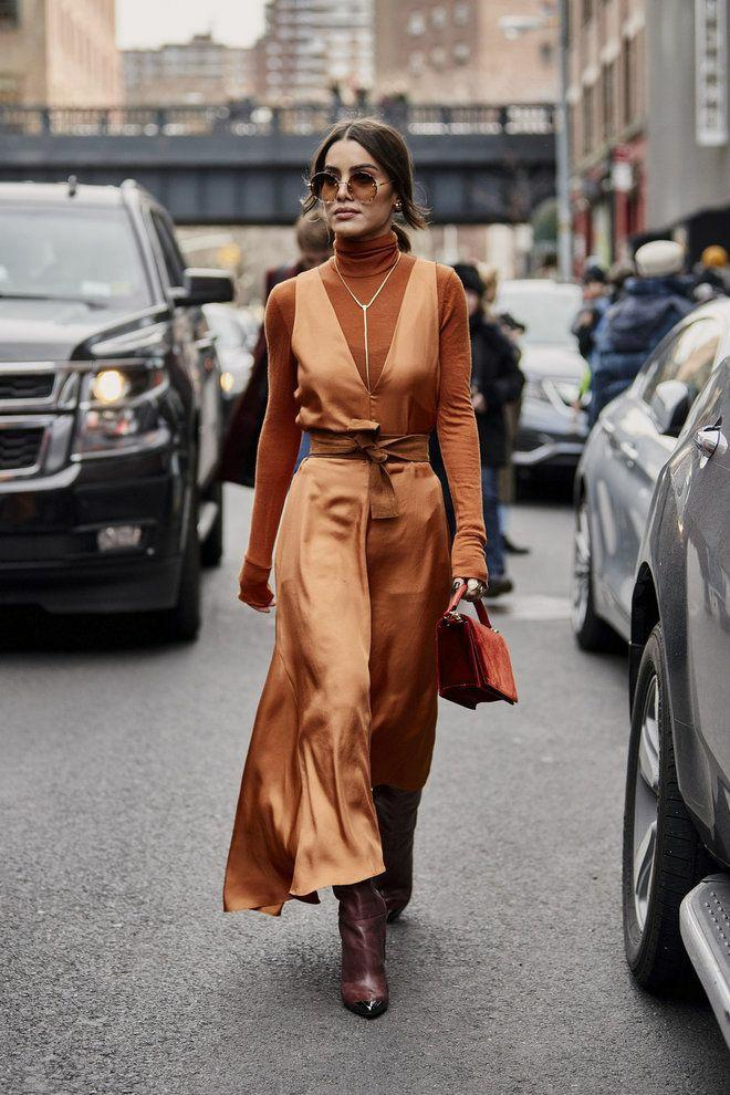 The girl is wearing a brown turtleneck with a high collar, a light brown silk maxi dress with a deep neckline and a brown belt