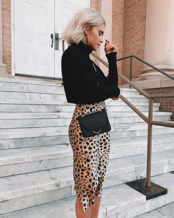 The girl is wearing a loose black turtleneck with a throat, a satin pencil skirt below the knee and with a leopard print, a black belt clutch bag.