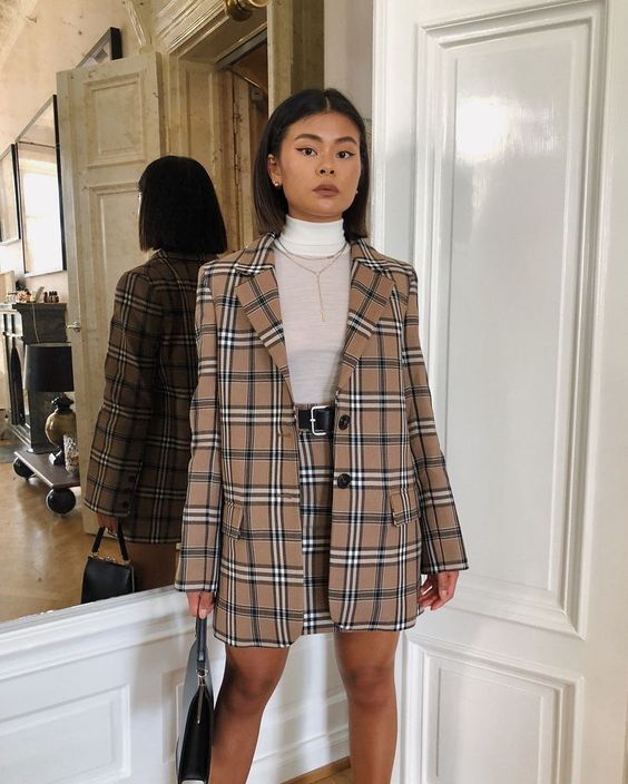 The girl is wearing a thin white turtleneck, a light brown Burberry check suit: a straight elongated jacket, a straight mini skirt with a black leather belt. The look is complemented by a long thin chain and a black clutch bag.