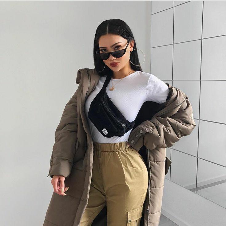 The girl is wearing a thin white turtleneck, mustard-colored bolognese pants, an oversized midi-length jacket