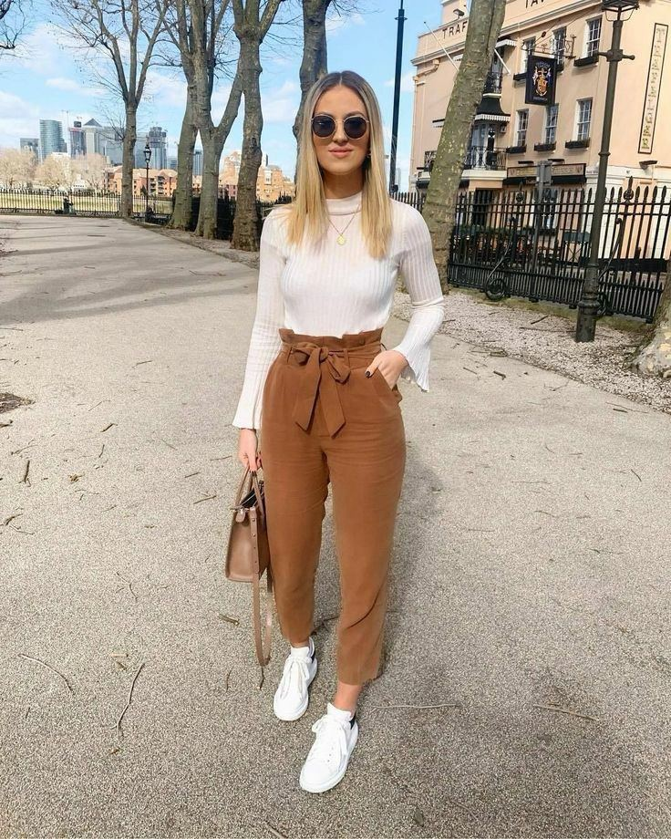 The girl is wearing a thin white turtleneck without a collar and with wide sleeves, brown corduroy banana trousers with a high gathered waist and a belt, white sneakers.