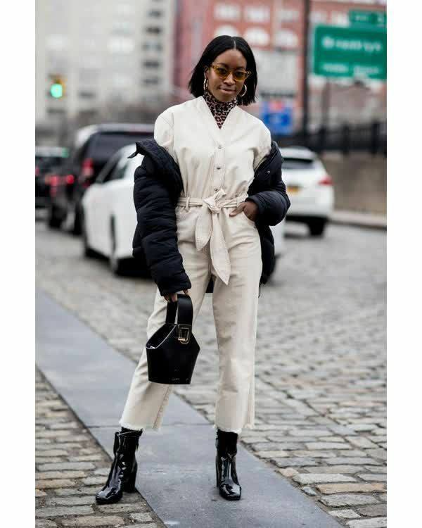 The girl is wearing a white cotton jumpsuit with a v-neck, a belt and buttons, a leopard-print turtleneck with a collar, patent ankle boots with thick high heels, a black puffy jacket. The image is complemented by a black leather bag of an unusual shape, light brown glasses and round earrings