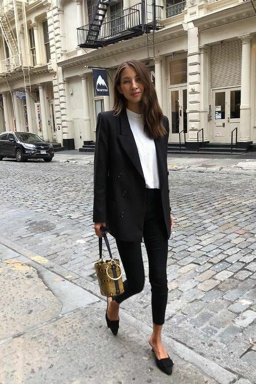 White turtleneck with a low collar in combination with a black oversized jacket, black skinny jeans, pointed toe and without heels, a brown sheath bag.