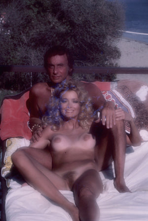 Divina Celeste and Bob Guccione laying naked in sun by beach