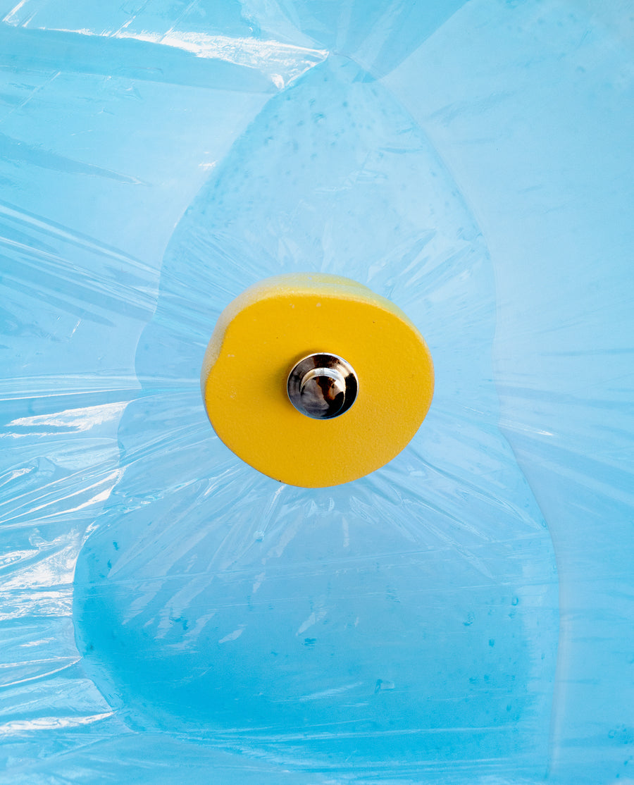 a yellow frisbee is in the blue water