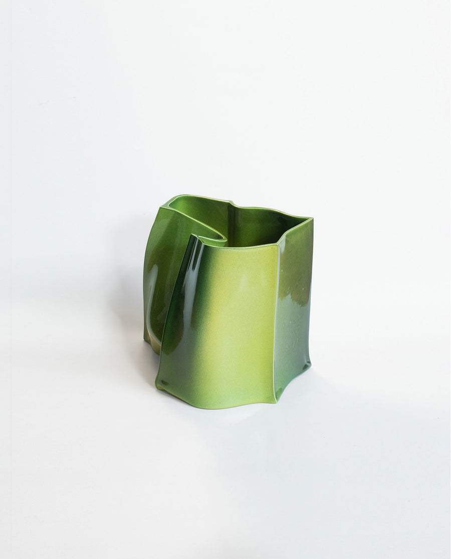 a green vase with a green plant in it