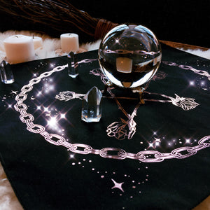 black altar cloth with a crystal ball and candles
