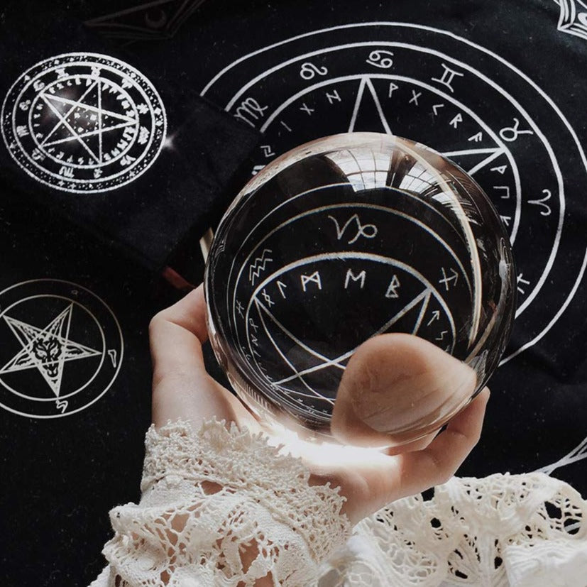 Hand holding a crystal ball displaying a black altar cloth with a pentagram, sigil and occult markings and a velvet grimoire spellbook.