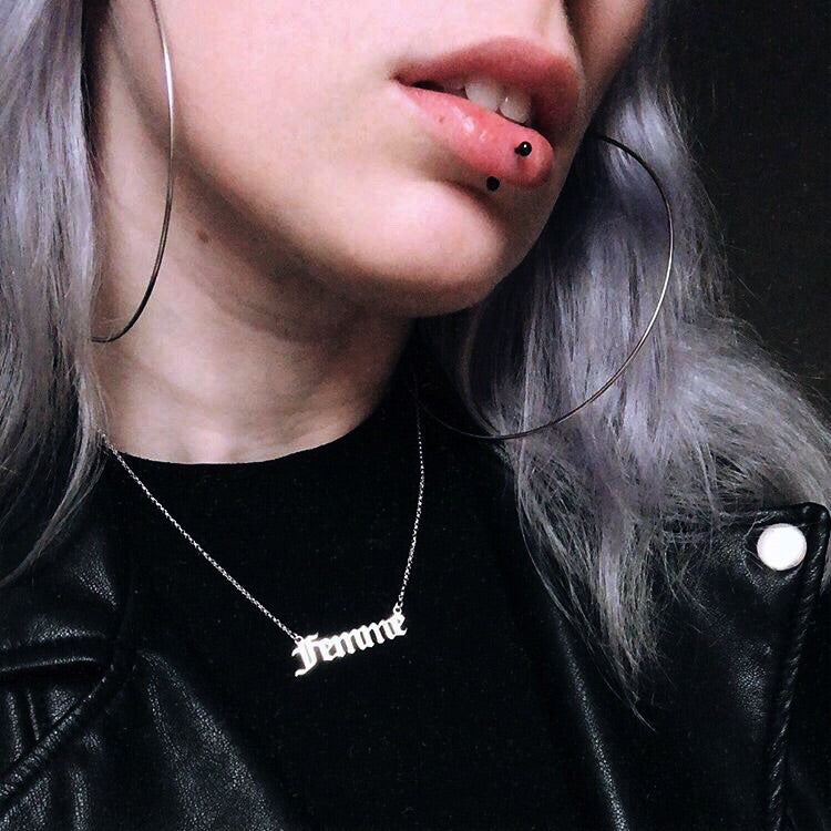 Gothic blackletter Femme Nameplate Necklace in sterling silver worn on a model with a black shirt