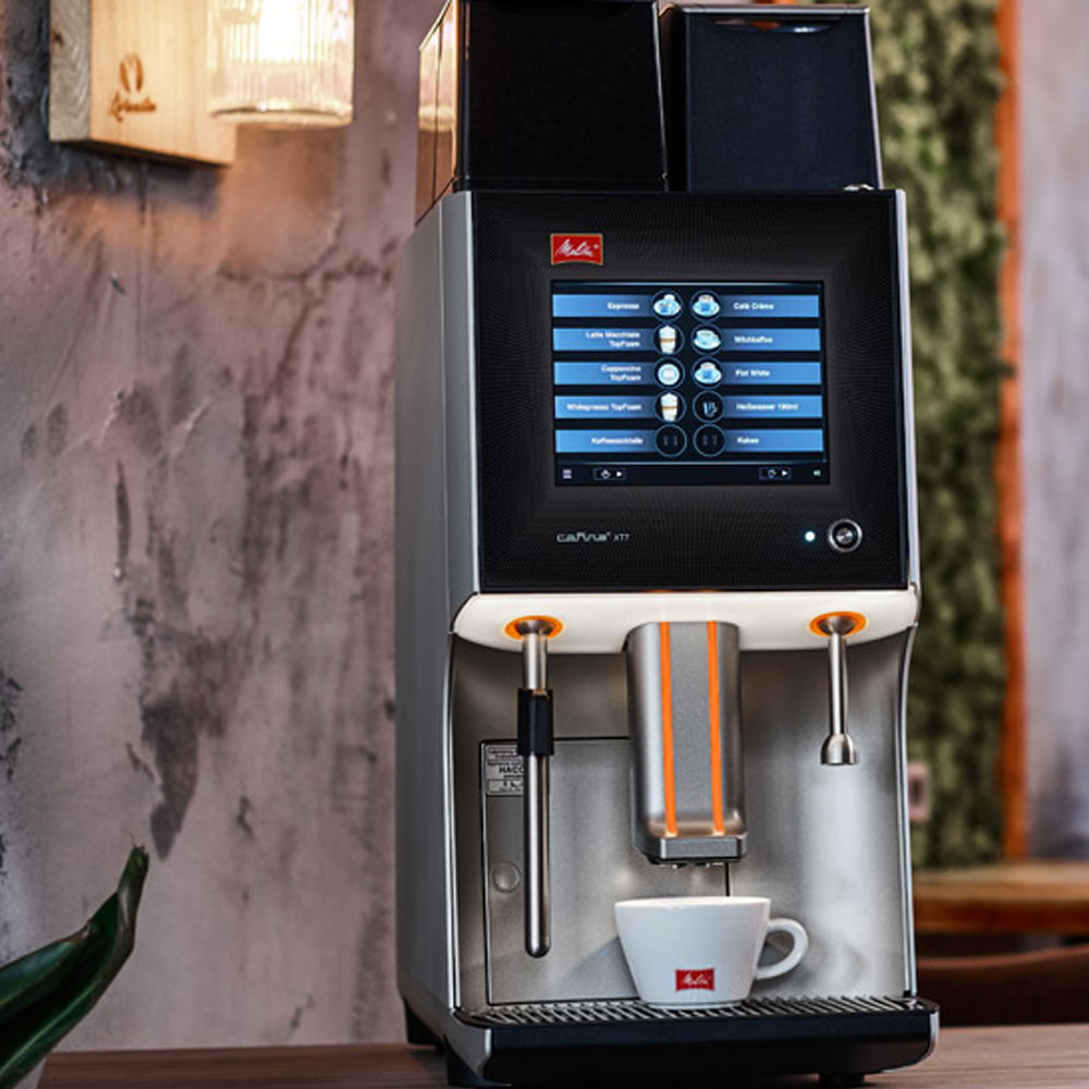 Melitta Cafina XT7 Bean To Cup Coffee Machine on a bar with a coffee cup