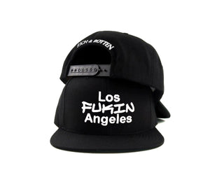 "Black snapback hat on white background. Embroidered white ""LOS FUKIN ANGELES"" in front and ""Rich & Rotten"" text on the back"