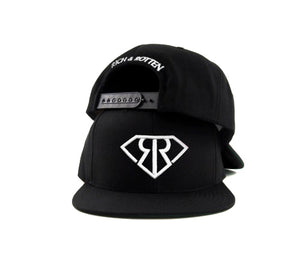 "Black snapback hat on white background. Embroidered white RR logo in front and ""Rich & Rotten"" text on the back"