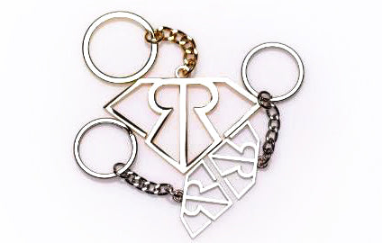 golden keychain in a shape of Rich and Rotten logo on white background