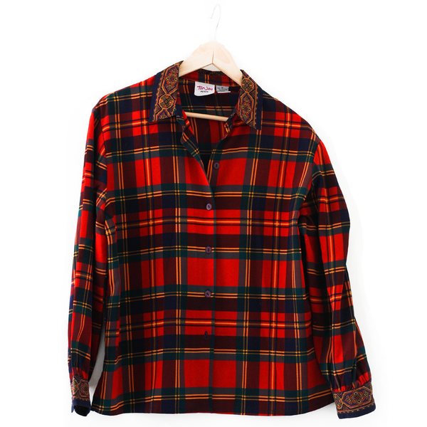 Red Plaid button down collard shirt, hanging on hangar in front of white background