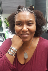Photo of founder Alaine Hutson with cornrowed hair chin resting on hand with three cuff bracelets on arm in a maroon scoop next shirt.