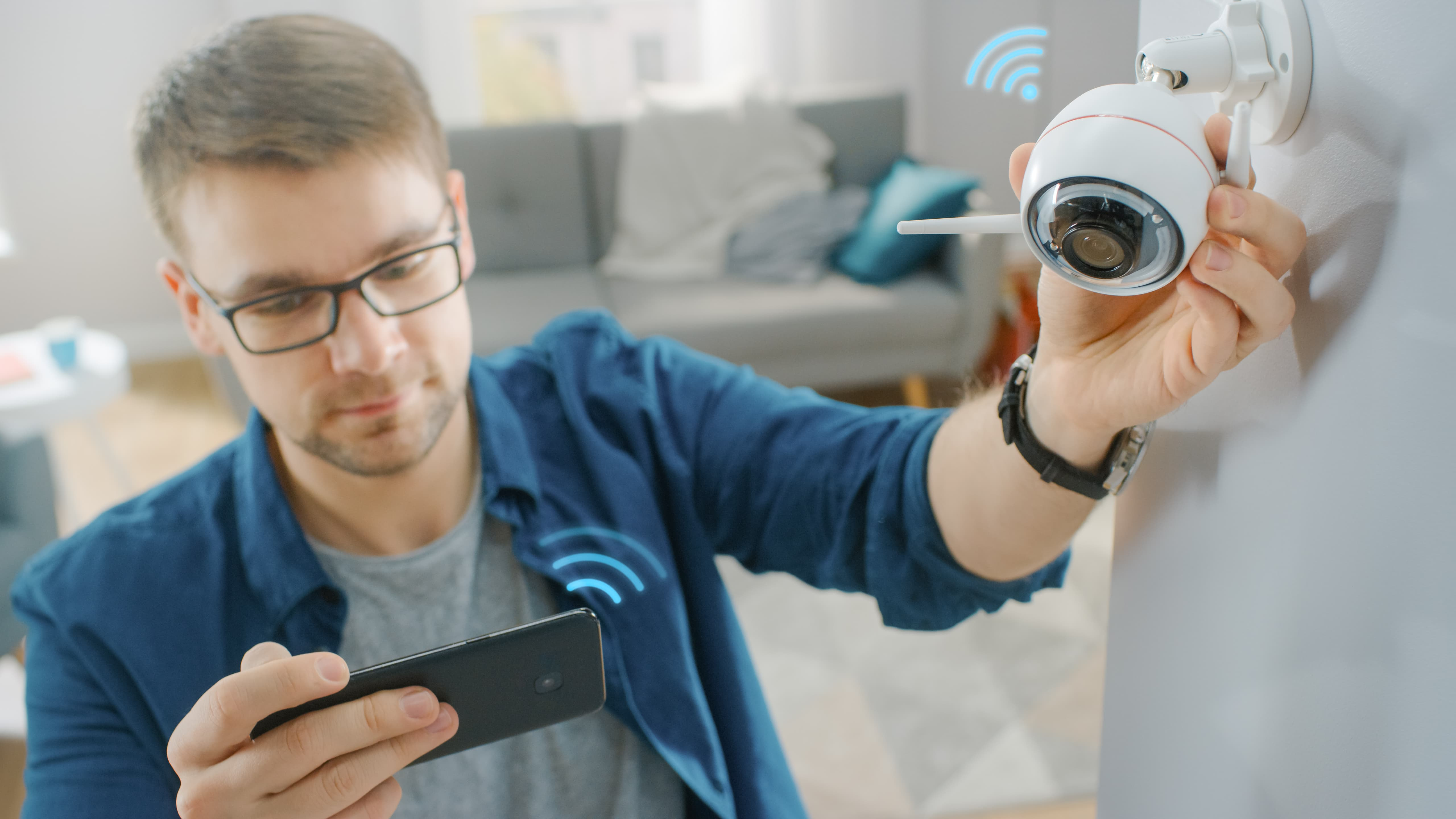 Man adjusting smart home security camera with phone