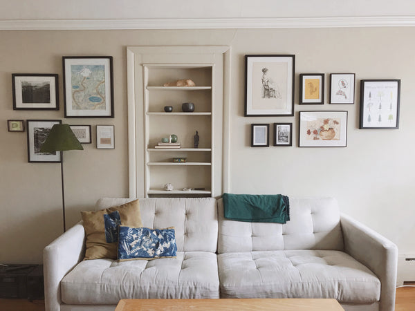 Intentional home decor: a collection of artworks displayed over a casually comfortable sofa.