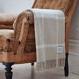 brown windowpane merino throw over the arm of a chair - bottle green homes
