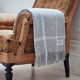 grey windowpane merino throw on the arm of a chair - bottle green homes