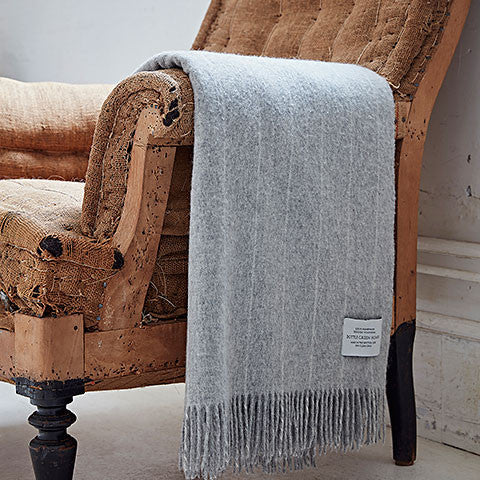 Grey pinstripe merino throw over arm of chair - bottle green homes