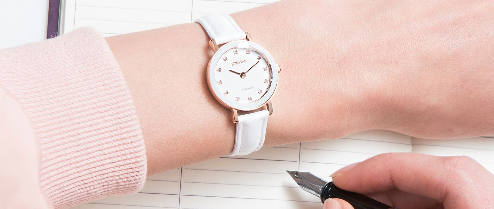 Woman writing on paper wearing an Aura Swiss ladies watch by Jowissa mobile version