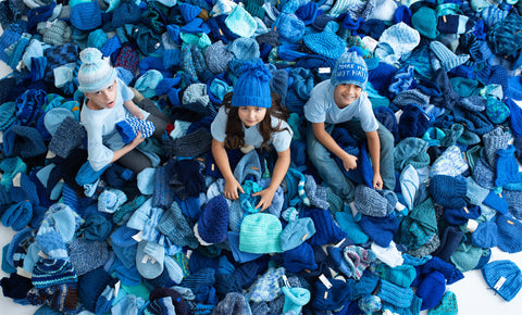 Children in a pile of blue hats