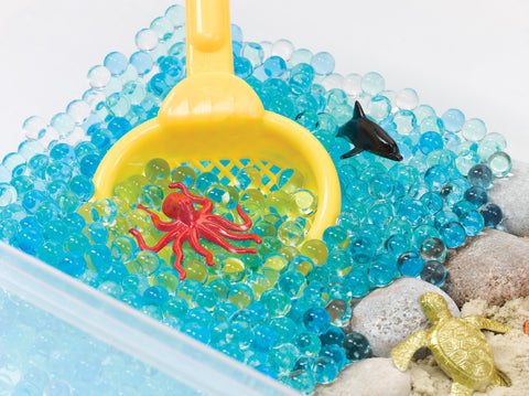 Sensory bin with water beads and a scoop