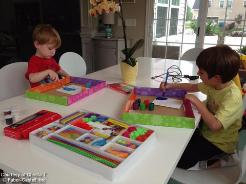 Two boys creating art at table