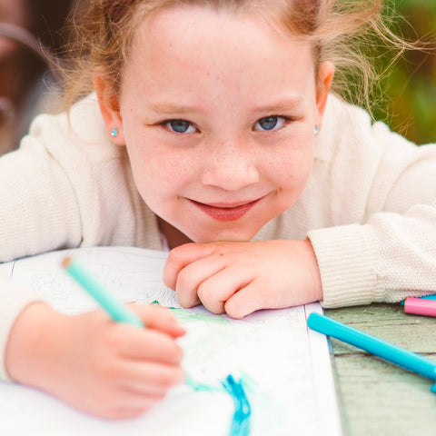 Small girl smiling and coloring with a marker