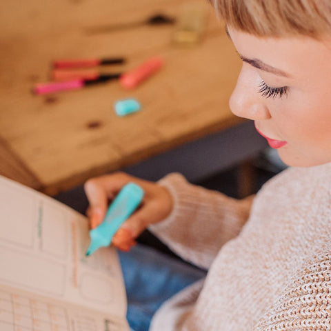 Woman using textliner highlighter in notebook