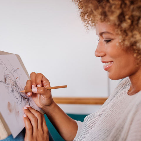 Woman sketching with monochrome pencils