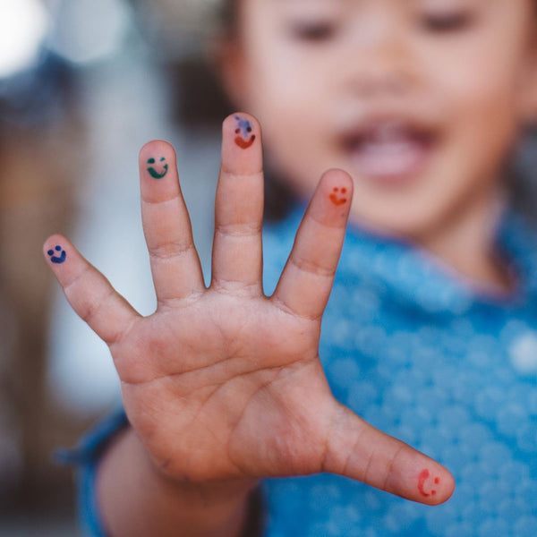 Child with smiley faces drawn on fingers