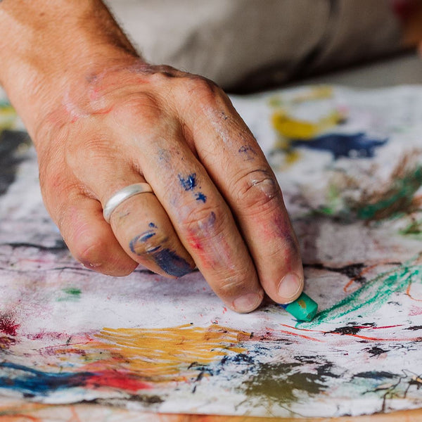 Hands using pastels to paint