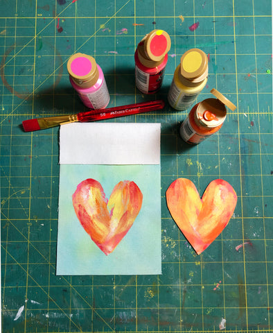 Watercolor fabric square with heart stamp and paints.