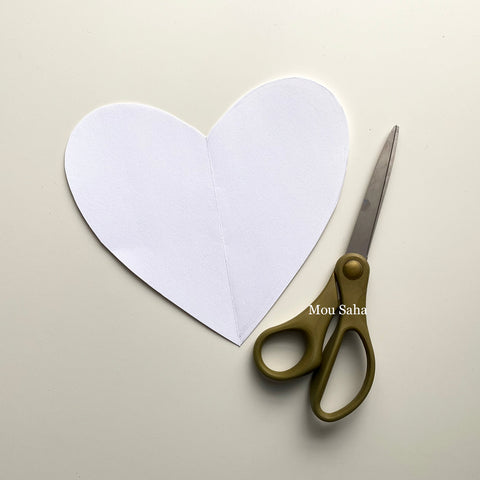Cut out paper heart with scissors