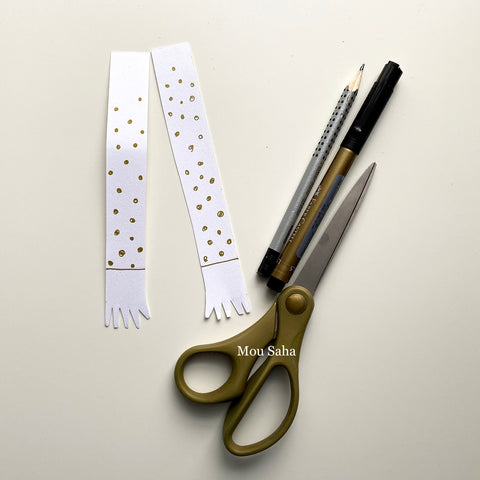 Two paper strips with a pencil, Pitt Artist Pen, and scissors