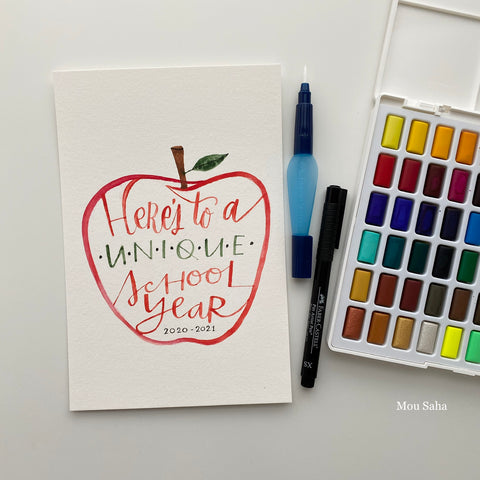 Watercolor pan with hand lettering in an apple