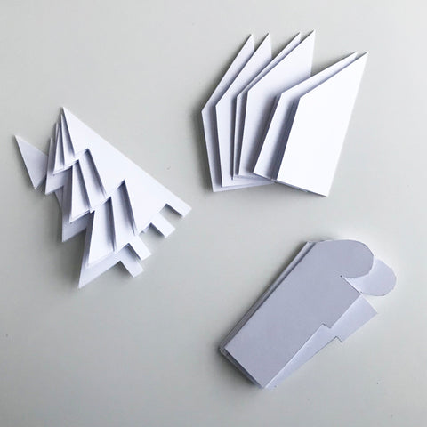 Paper cut in the shape of a tree, house, and Christmas present