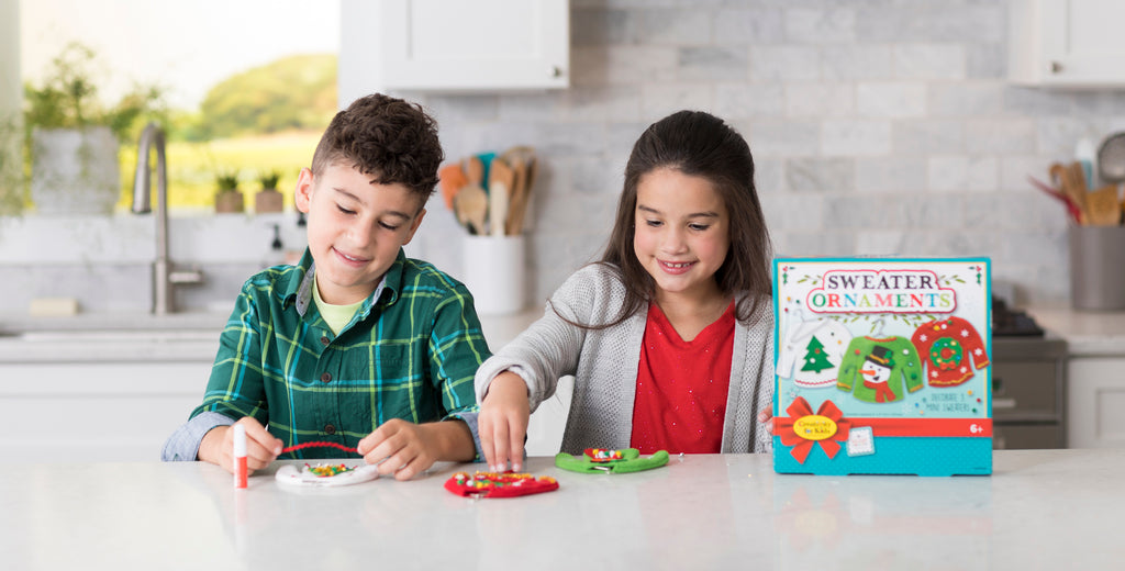 Boy and Girl crafting Christmas sweater ornaments