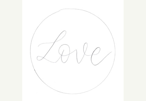 White tag with hand lettered love and circle