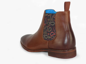 Side view of brown leather chelsea boots with paisley patterned insert