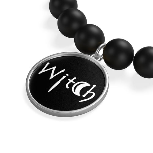 The word Witch in white creepy letters on a black bracelet