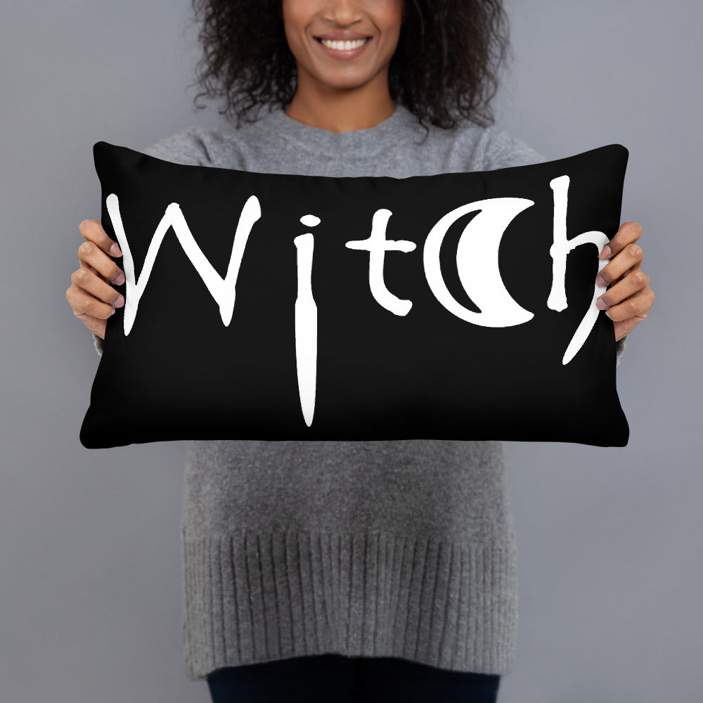 The word Witch in white creepy letters on a black pillow