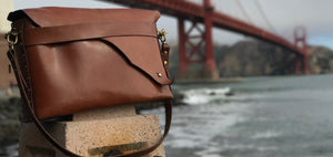 Full Grain Leather Bag For Men and women by Paulcity Goods. This photo shows the bag as it rests on a fencepost at Fort Point in San Francisco. Handmade in San Francisco this bag sits beautifully in front of the iconic Golden Gate Bridge.