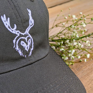 Front View Closeup of 'Dad Hat' style hat with unseen creatures logo with decorative weeds
