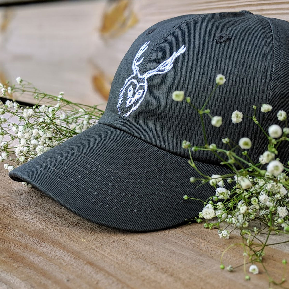 Front Left view of 'Dad Hat' style hat with unseen creatures logo with decorative weeds