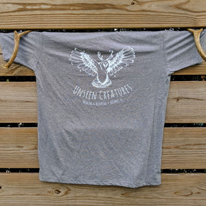Mens T Shirt Grey With Unseen Creatures Logo in White In Center Chest Hung on a wooden fence with decorative antlers